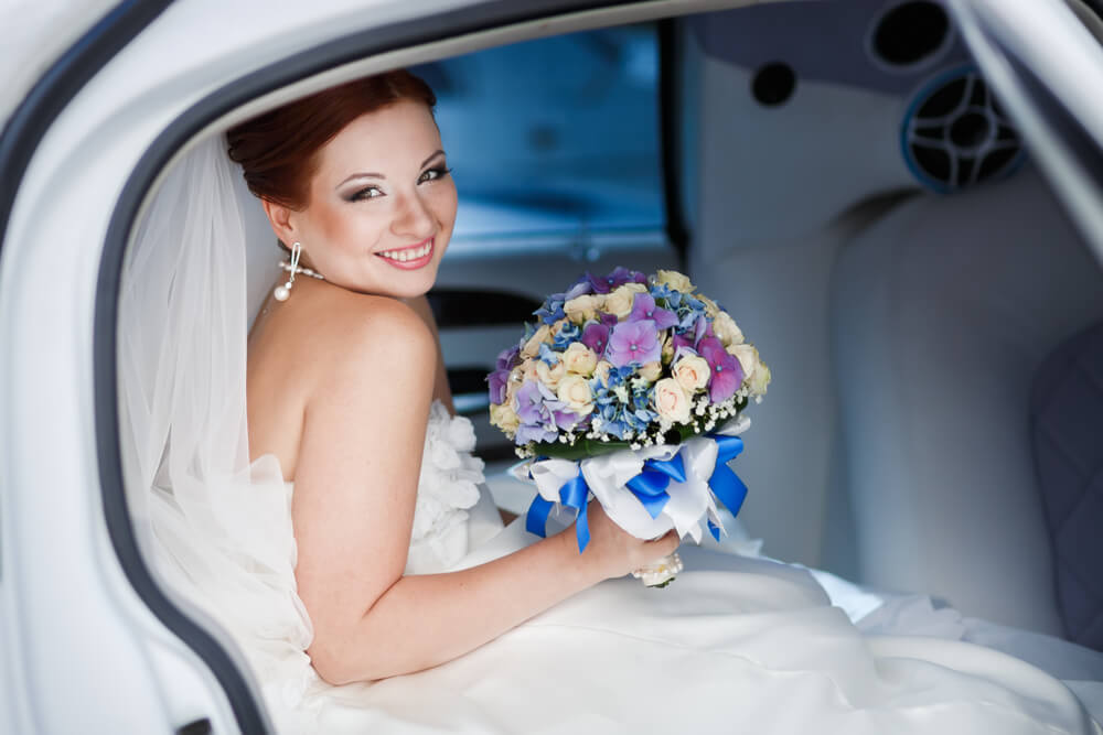 Bride in white wedding limo with colorful bouquet in Phoenix